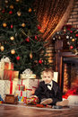 Kids xmas little boy playing with toys at home near the fireplace and christmas tree Stock Images
