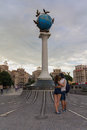 Kiev, Ukraine - June 16, 2016: Young couple with a monument with a globe
