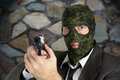 Killer in camouflage mask is aiming with a pistol the Stock Images