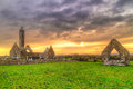 Kilmacduagh monastery with stone tower at sunset Royalty Free Stock Photo