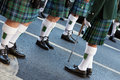 Kilts and ghillie brogues legs of traditional irish bagpipes players wearing black shoes intricate white woollen socks pleated Stock Images