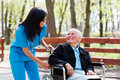 Kind doctor chatting with elderly lady beautiful nurse in blue coat walking a in wheelchair in park Royalty Free Stock Photo