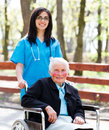 Kind nurse with elderly lady in wheelchair beautiful doctor blue coat walking a park Royalty Free Stock Photos