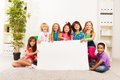 Kindergarten advertising group of little kids sitting in the living room with blank banner Stock Image