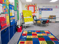 Kindergarten classroom interior with calendar bulletin board table chairs and alphabet rug Royalty Free Stock Photos