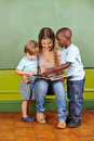 Kindergarten teacher and children nursery reading a book together in Royalty Free Stock Photos