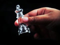 The king in hand clear glass chess piece a against black background Stock Photography