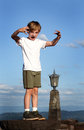 King of the mountain winner a young boy exuberant as accomplished while standing on a high wall blue cloudy sky in background Stock Image