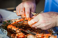 King prawns and oily fingers close up image of a pair of hands cracking open size prawn Stock Photography