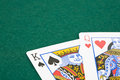 King and queen playing cards closeup of of hearts of spades over green felt surface Royalty Free Stock Images