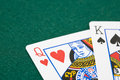 King and queen playing cards closeup of of hearts of spades over green felt surface Royalty Free Stock Image