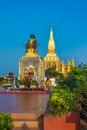 King setthathirat statue and pha that luang stupa in evening great is a gold covered large buddhist in Royalty Free Stock Photography