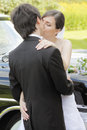 Kiss bride and groom kissing outdoors at the car Stock Photos