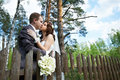 Kiss bride and groom about wooden fence Royalty Free Stock Images