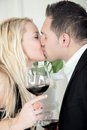 Kiss a couple is kissing while celebrating there first date with a glass of red wine Royalty Free Stock Photography