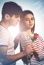 Kiss and make up boy gives girl a red rose Stock Photo