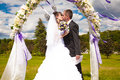 Kiss under arch first of newly married couple wedding Stock Photo