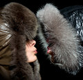 Kiss in the winter of men and women fur hoods Royalty Free Stock Images
