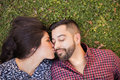 Kissing boyfriend in the cheek beautiful young women relaxing with her and him on Royalty Free Stock Image
