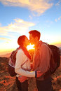 Kissing couple romantic lovers hiking at sunset sharing kiss enjoying sunshine and love on beautiful hike in mountain nature Stock Image