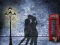 Kissing couple silhouette in the streets of london night scenery with glooming lantern and british phone box retro style with dark Royalty Free Stock Photography