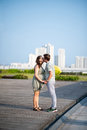 Kissing expecting couple holding hands and outdoors Royalty Free Stock Image