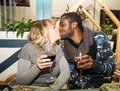 Kissing happy couple black man and white woman with glass of wine men women at party Stock Photos