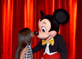 Kissing mickey mouse having his picture taken with a pretty little girl the little girl is mickeys nose in the meet Stock Photography