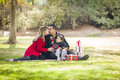 Kissing mixed race family enjoying christmas gifts young in the park together Royalty Free Stock Photography