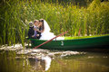 Kissing in reed newly married couple boat Stock Images