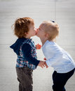 Kissing toddlers side view standing of two caucasian blonde girl and red haired boy Stock Photos