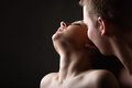 Kissing young couple dark background Royalty Free Stock Photography