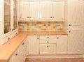 Kitchen cupboards new showing cream colored wooden and drawers and large glass fronted cupboard for glasses with multicolored Stock Photography