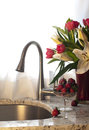 Kitchen faucet strawberries and fresh flowers on a counter with Royalty Free Stock Images