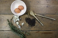 Kitchen ingredients comprising of brown eggs in a white bowl garlic fresh rosemary and black lentils with two wooden spoons all Royalty Free Stock Photography