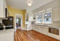 Kitchen interior with white cabinets, yellow walls and wood floor Royalty Free Stock Photo