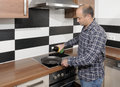 Kitchen man putting oil in frying pan Stock Images