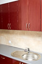 Kitchen metal sink work surfaces wooden cabinets Stock Image