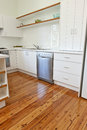 Kitchen with polished floorboards a white cupboards and pollished wood floor Royalty Free Stock Photo