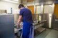 Kitchen porter washing up at sink