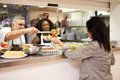 Kitchen serving food in homeless shelter to woman Royalty Free Stock Photo
