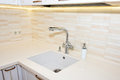 Kitchen sink and faucet. Modern, bright, clean kitchen interior details. Royalty Free Stock Photo