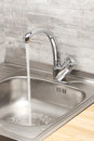 Kitchen sink with running tap water Royalty Free Stock Photo