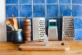 Kitchen still life. Vintage utensils. kitchenware graters, ceramic jug, spoons. cutting board. Blue tiles wall. wooden Royalty Free Stock Photo