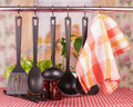 Kitchen tableware on hooks over background Stock Images