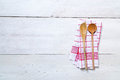 Kitchen towel background with wooden spoons red cooking on light wood Royalty Free Stock Photo