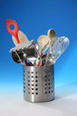 Kitchen utensils in metal holder stainless steel container with tools on a blue background whisk wooden spoons potato masher Stock Photos