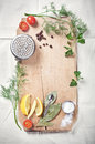 Kitchen utensils spices and herbs for cooking fish on wooden cutting board with space text Royalty Free Stock Photography
