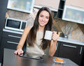 Kitchen woman using a tablet computer while drinking tea in her Royalty Free Stock Photo