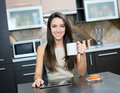 Kitchen woman using a tablet computer while drinking tea in her Stock Photography